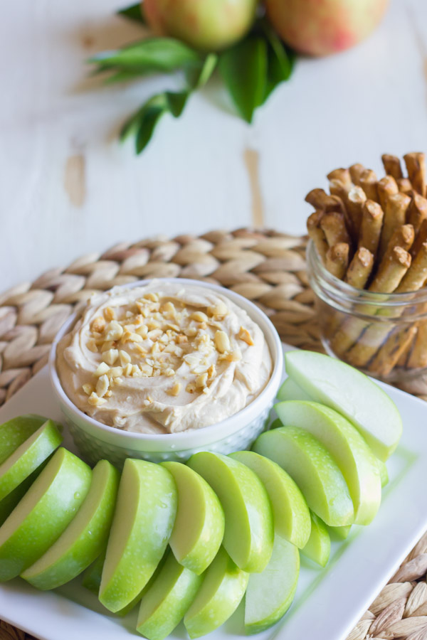 Greek Yogurt Peanut Butter Dip in a bowl, sitting on a serving platter with sliced apples, and a glass jar of stick pretzels next to it.