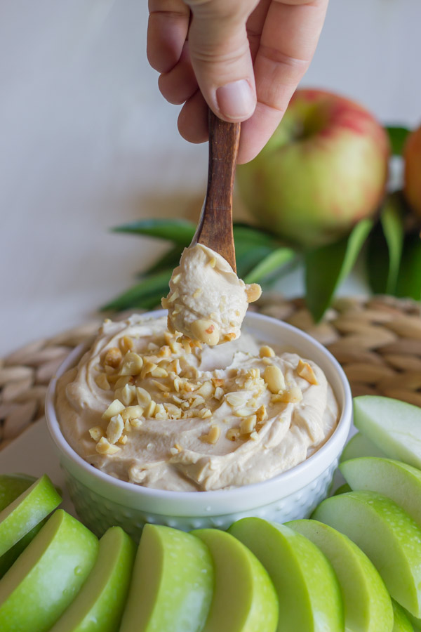 Greek Yogurt Peanut Butter Dip in a bowl, sitting on a serving platter with sliced apples, and a tiny spoon with dip on it.