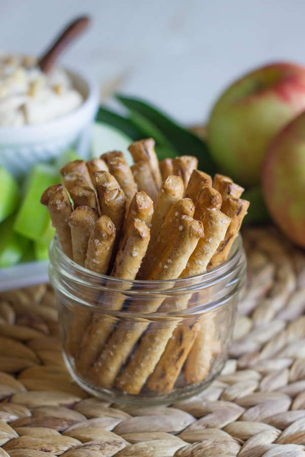 A glass jar of stick pretzels, with Greek Yogurt Peanut Butter Dip in a bowl sitting on a serving platter with sliced apples in the background, along with some whole apples.