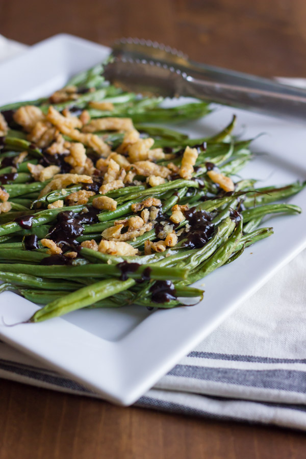 Roasted Green Beans with Creamy Cranberry Balsamic topped with french friend onions on a serving plate with tongs.
