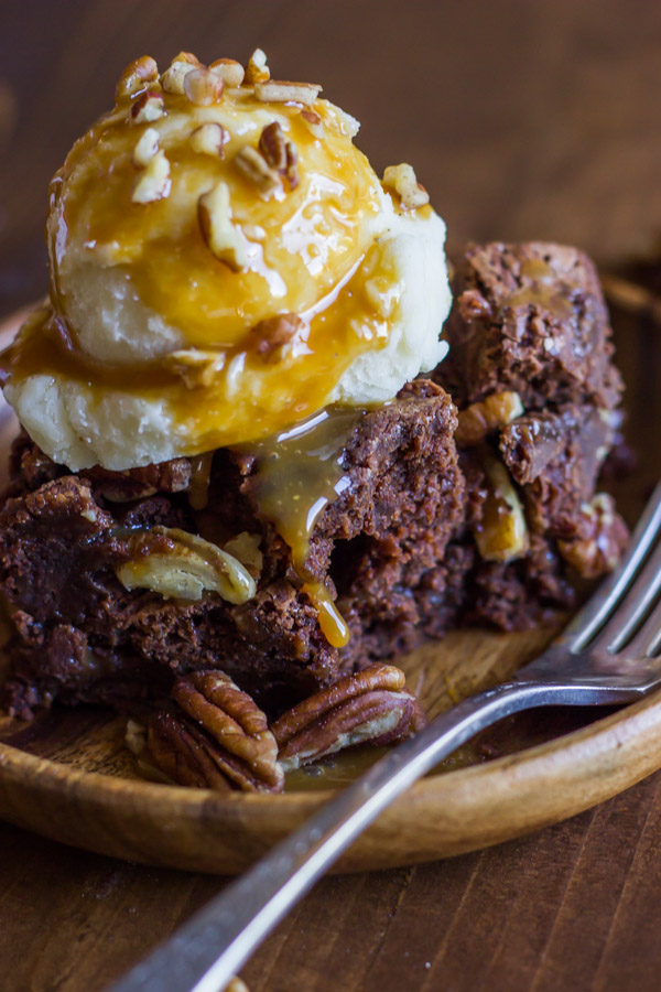 Copycat Zupas Rockslide Brownie on a plate, topped with a scoop of ice cream, caramel sauce and chopped pecans.