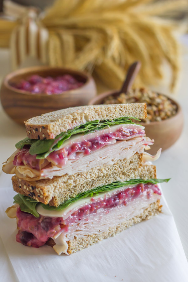 Turkey And Cranberry Sandwich cut in half, with the halves stacked on top of each other.