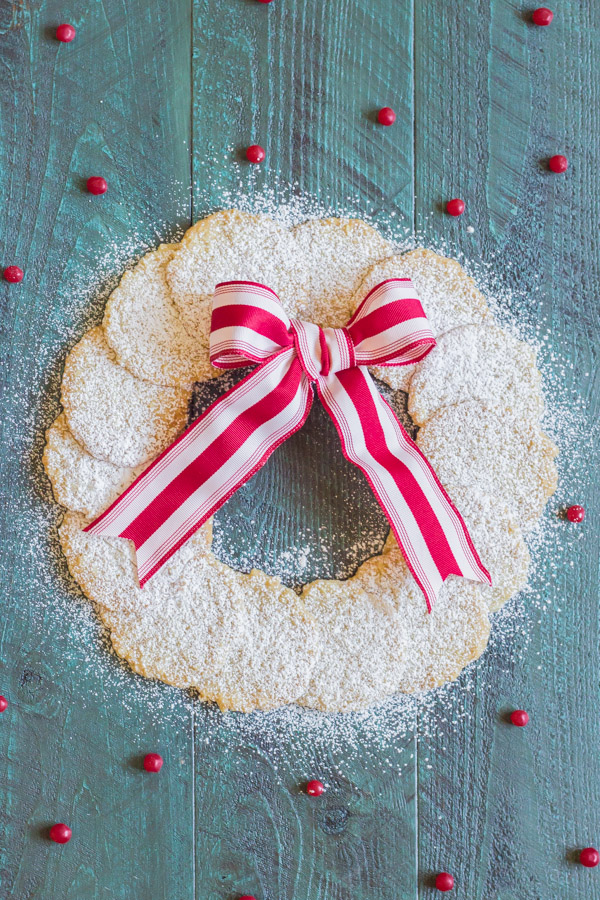 Christmas Oatmeal Cookies dusted with powdered sugar and arranged in a circle to look like a wreath with a red and white striped bow.