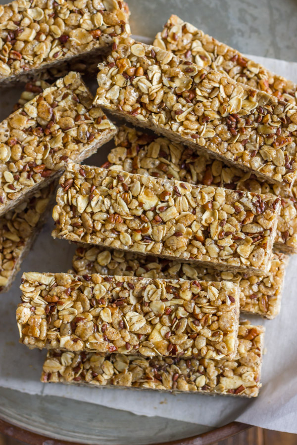 Healthy Chewy Apple Cinnamon Granola Bars stacked on a piece of parchment paper.