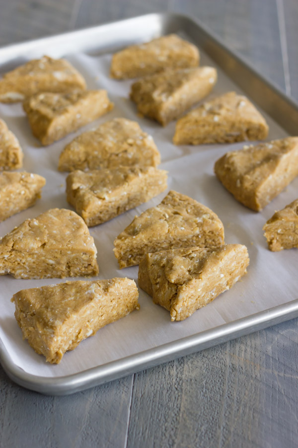 Gingerbread Oat Scones dough wedges arranged on a parchment paper lined baking sheet.