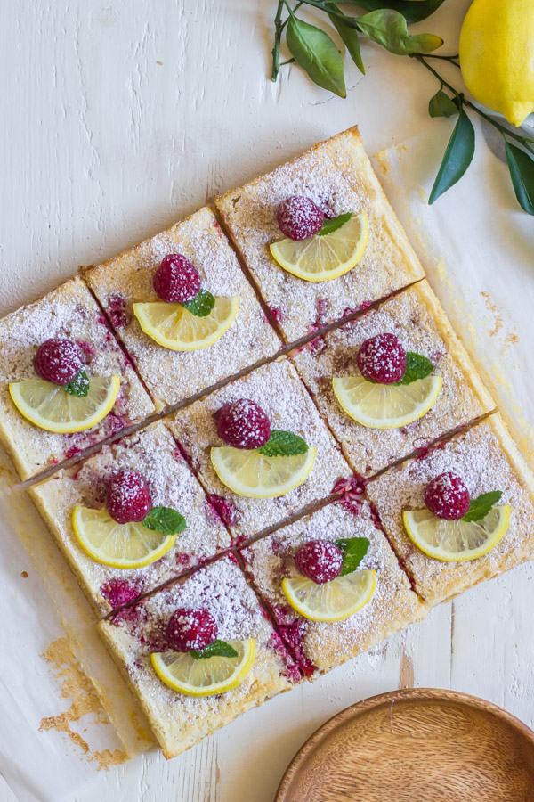 Raspberry Lemon Bars cut into squares, each one garnished with a lemon slice, a whole raspberry and a mint leaf.