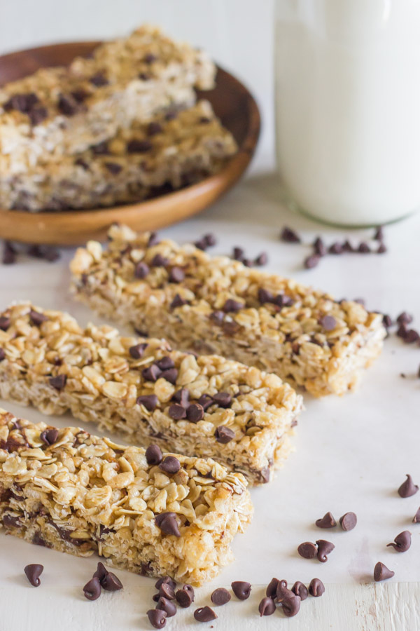 Three Copycat Quaker Chewy Chocolate Chip Granola Bars next to each other, with a glass of milk and more bars on a plate in the background, and chocolate chips sprinkled around.