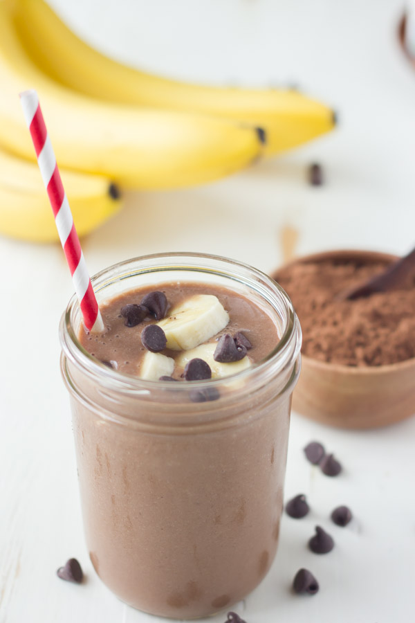 Chocolate Banana Smoothie topped with banana slices and chocolate chips, in a glass jar with a straw, with a small bowl of cocoa powder and a bunch of whole bananas in the background.