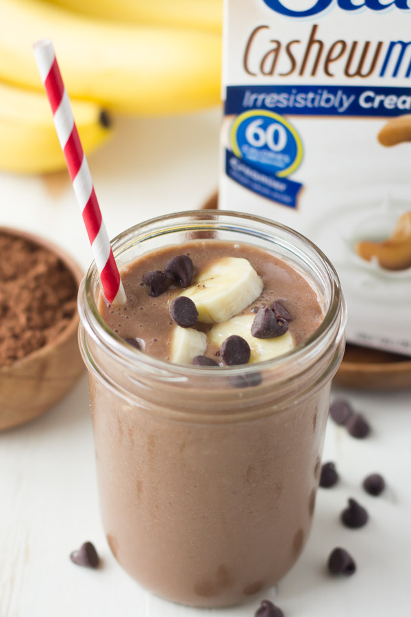 Chocolate Banana Smoothie topped with banana slices and chocolate chips, in a glass jar with a straw, with a small bowl of cocoa powder, a bunch of whole bananas and a carton of Silk Cashewmilk in the background.