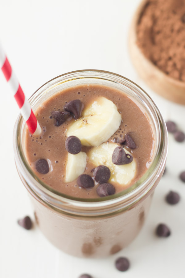 Chocolate Banana Smoothie topped with banana slices and chocolate chips, in a glass jar with a straw.