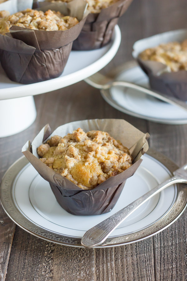 Healthier Cinnamon Oat Streusel Muffin in a parchment paper muffin liner on a plate, with more muffins on a cake stand in the background along with another muffin on a plate.