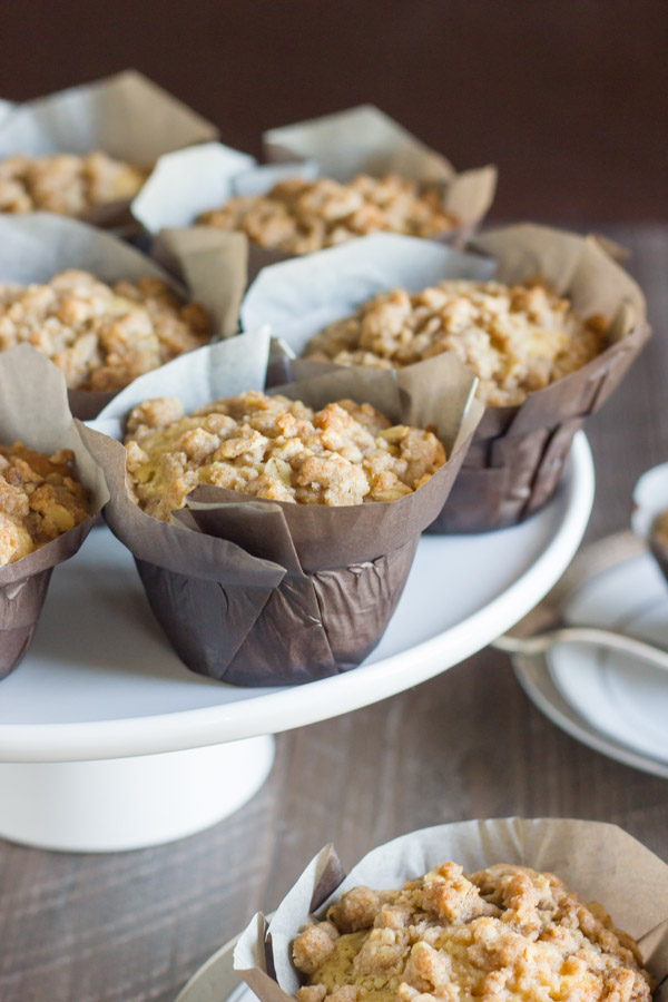 Healthier Cinnamon Oat Streusel Muffins in parchment paper muffin liners on a cake stand.