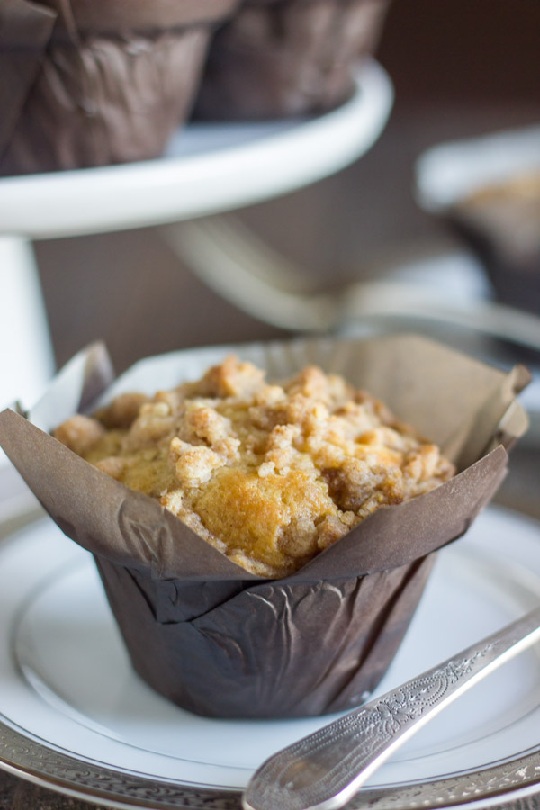 Healthier Cinnamon Oat Streusel Muffin in a parchment paper muffin liner on a plate.