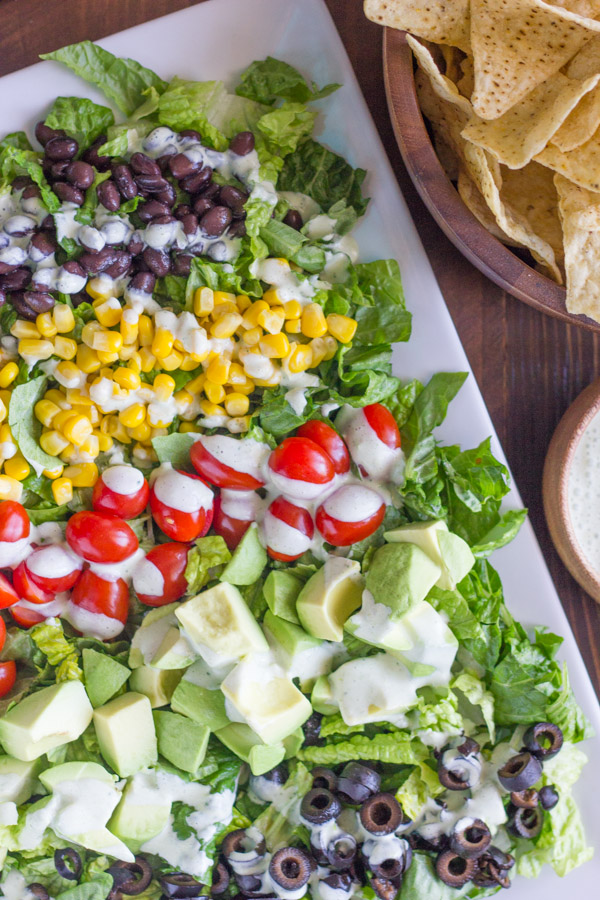 Healthy Chopped Taco Salad on a serving platter, with a bowl of tortilla chips and a small bowl of creamy cilantro lime dressing next to the platter.