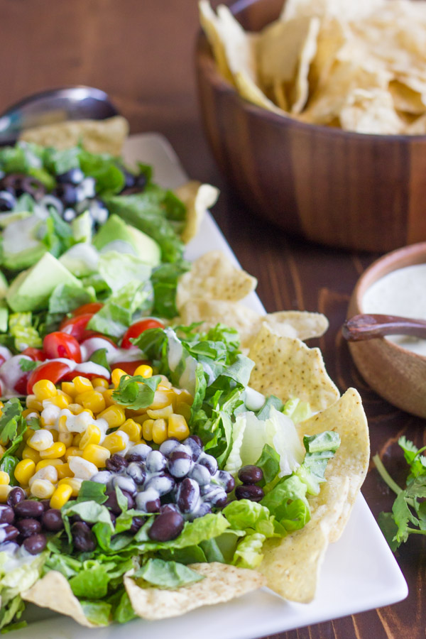 Healthy Chopped Taco Salad on a serving platter with some tortilla chips, with a small bowl of creamy cilantro lime dressing and a bowl of tortilla chips next to the platter.
