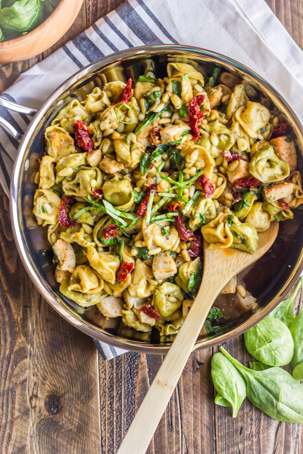 One Skillet Chicken Tortellini in a skillet with a wooden spoon.