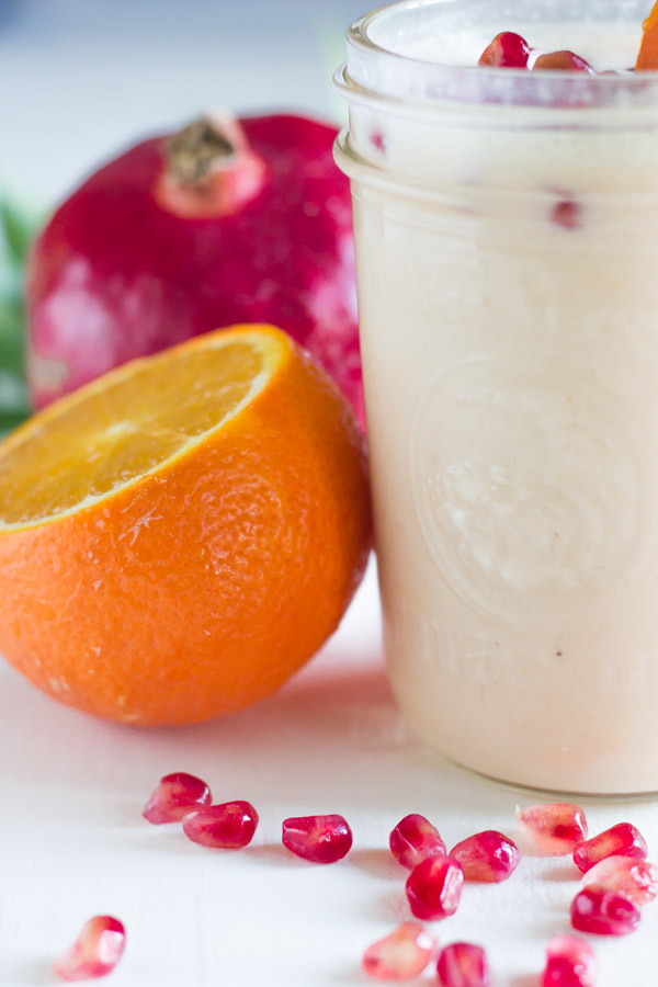 Pomegranate Citrus Smoothie in a glass jar with pomegranate seeds on top, with an orange and pomegranate next to the glass.