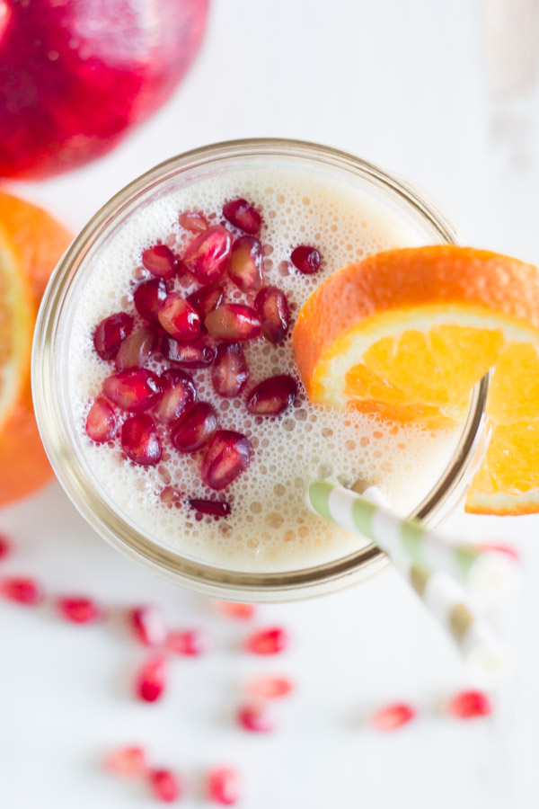 Pomegranate Citrus Smoothie in a glass jar with pomegranate seeds on top, an orange slice on the rim of the glass and two straws in it.