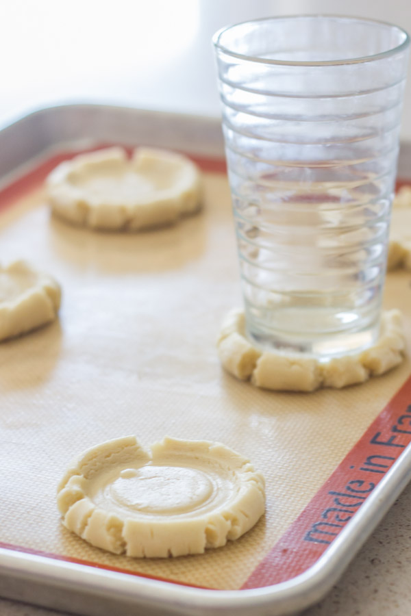 Swig Style Frosted Sugar Cookie smashed dough on a Silpat lined baking sheet, with a glass cup on top of one of them.