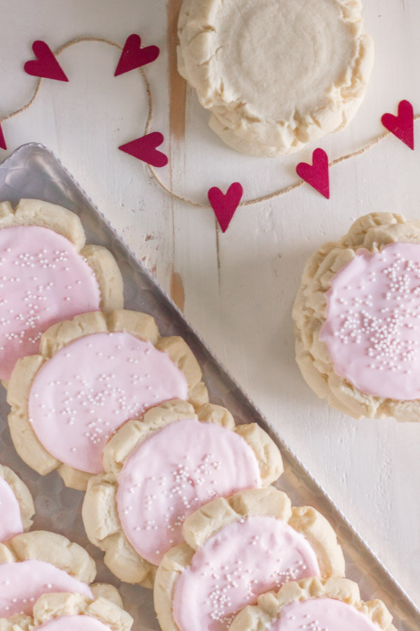 Swig Style Frosted Sugar Cookies arranged on a serving tray, with an unfrosted cookie and a frosted cookie next to the tray.