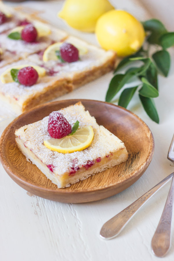 Raspberry Lemon Bar square serving on a wood plate, garnished with a lemon slice, a whole raspberry and a mint leaf.