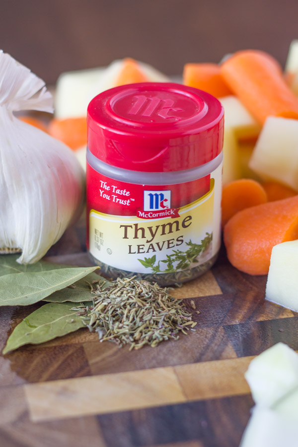 A spice container of McCormick Thyme Leaves on a cutting board with other ingredients for the Irish Beef Stew.