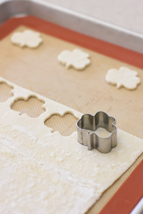 Puff pastry on a Silpat lined baking sheet, with a shamrock cookie cutter making the Shamrock Croutons.
