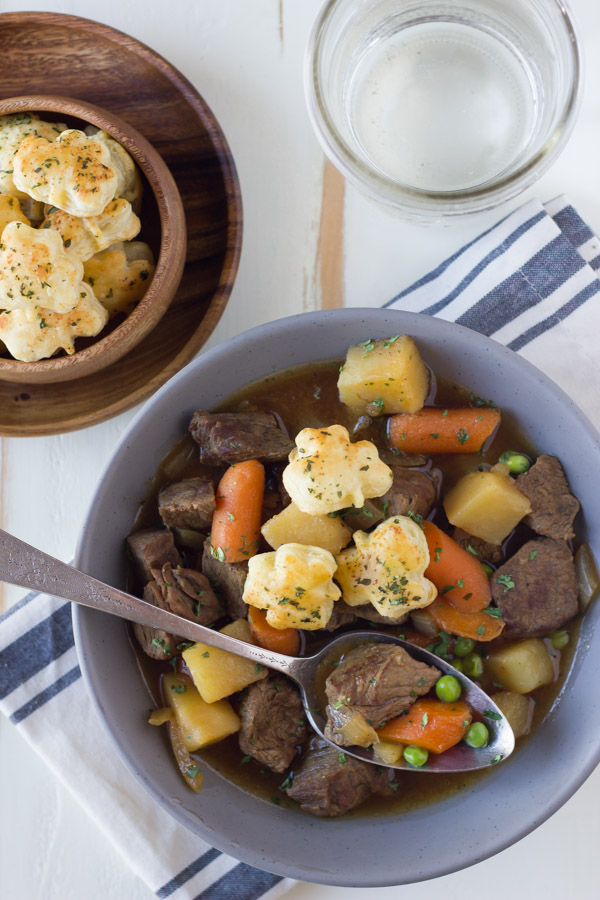 Irish Beef Stew in a bowl with a spoon and a wood bowl of Shamrock Croutons next to it, along with a glass of water.