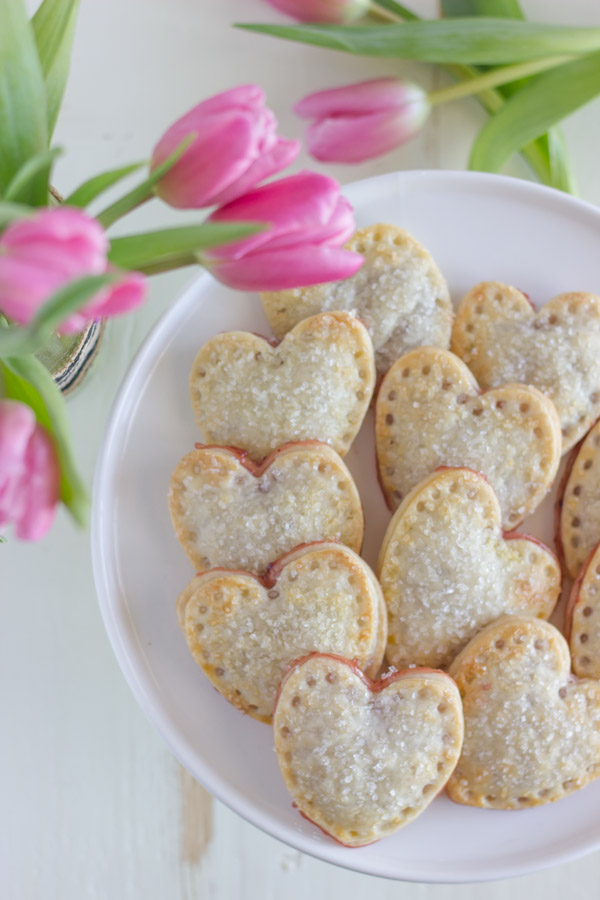 Strawberry Pie Hearts arranged on a cake stand, sitting next to some pink tulips.