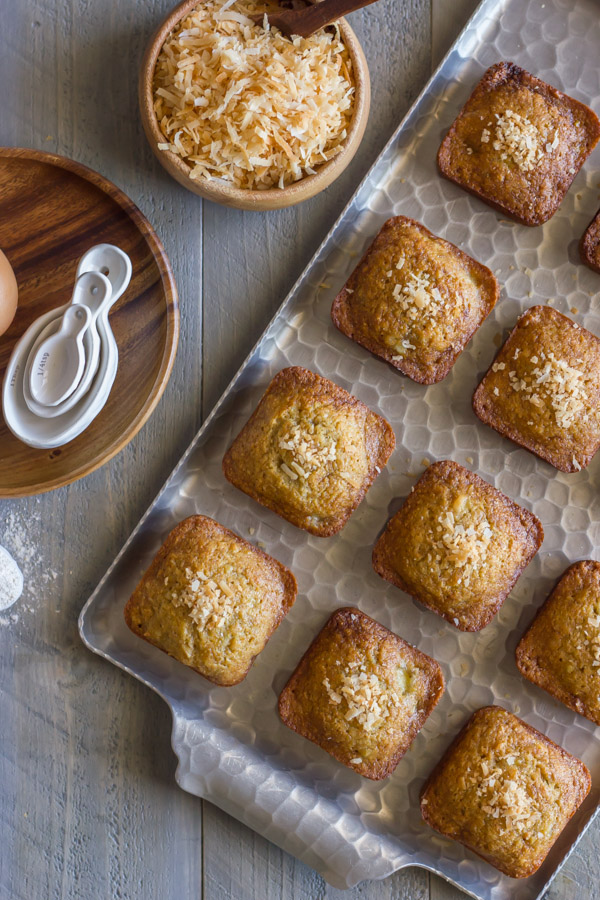Whole Wheat Toasted Coconut Banana Muffins on a serving platter, with a bowl of toasted coconut sitting next to the platter, along with a wood plate with measuring spoons on it.