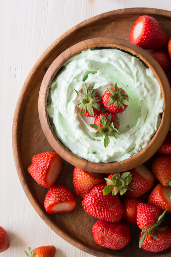 Creamy Pistachio Fruit Dip in a wood bowl topped with three whole strawberries, sitting on a wood plate with more whole strawberries.