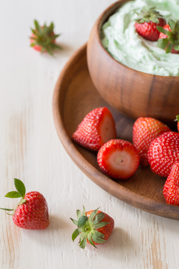 Creamy Pistachio Fruit Dip in a wood bowl topped with a few whole strawberries, sitting on a wood plate with more whole strawberries.
