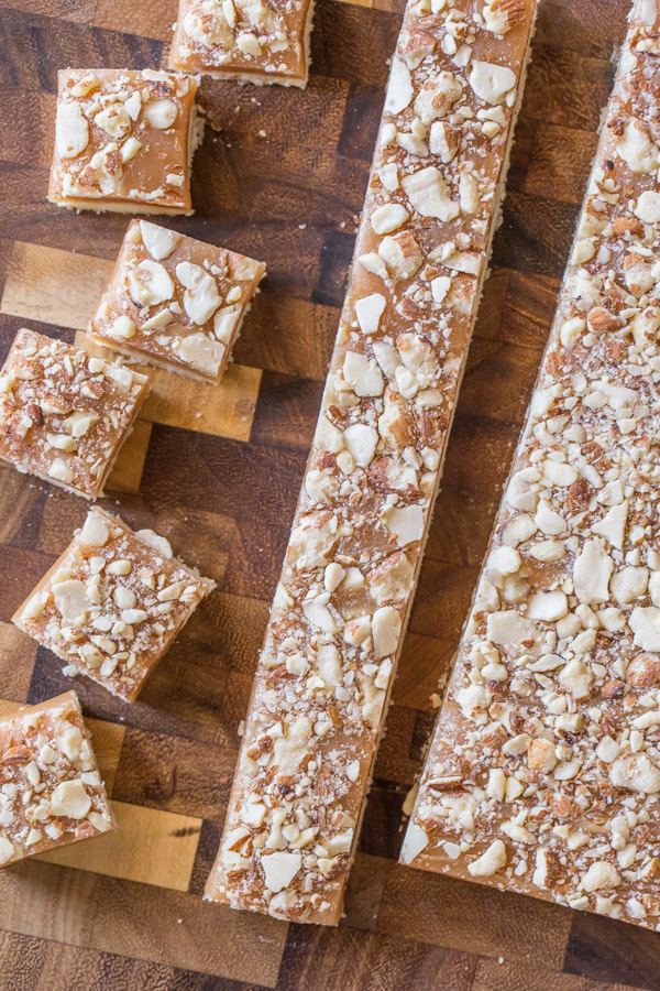 Homemade Caramel Almond Shortbread Bites being cut into squares on a cutting board.