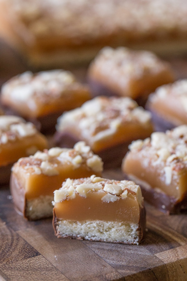 Homemade Caramel Almond Shortbread Bite cut in half, sitting on a cutting board with more Homemade Caramel Almond Shortbread Bites.