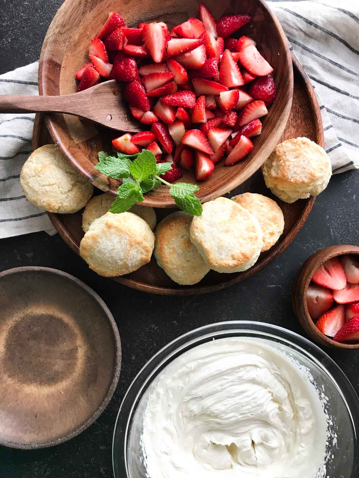 All the ingredients for the Homemade Strawberry Shortcakes ready to be assembled - a bowl of strawberries sitting on a plate with buttermilk biscuits and a bowl of whipped cream.