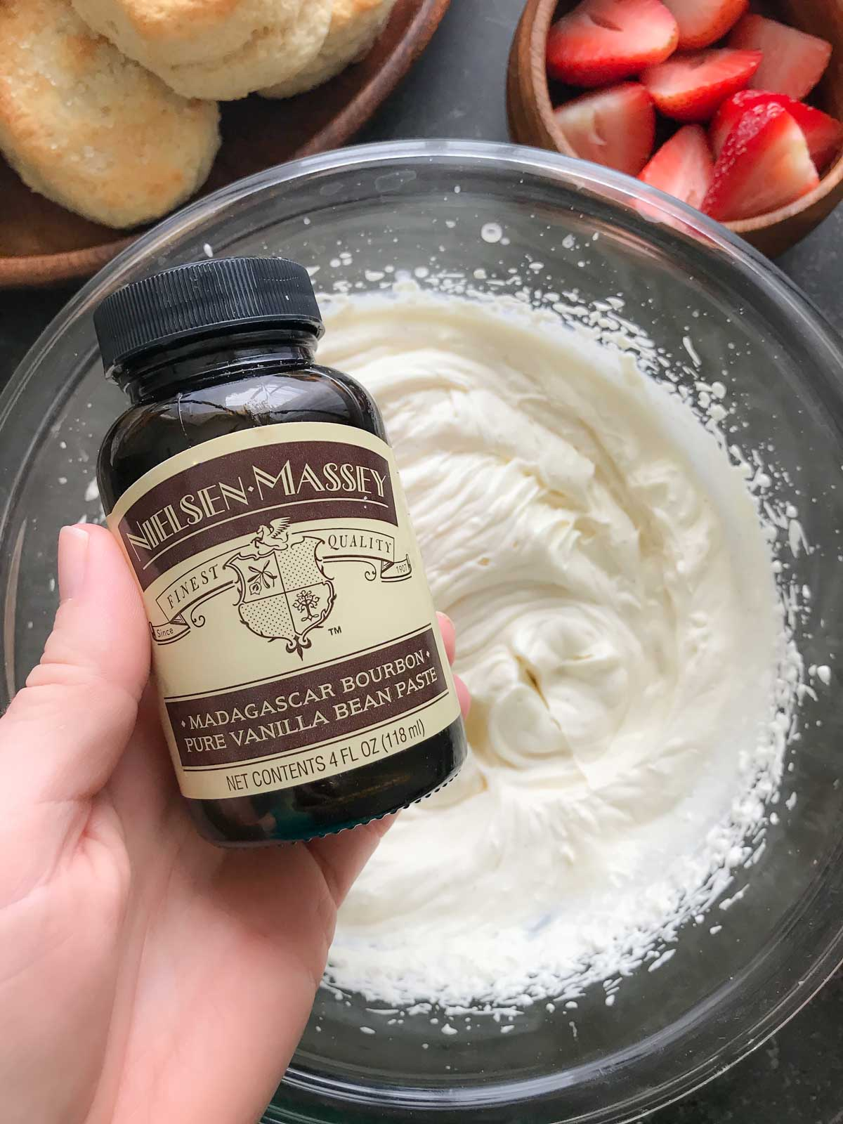 A jar of Madagascar Bourbon Vanilla Bean Paste from Nielsen Massey held over a bowl of homemade whipped cream.
