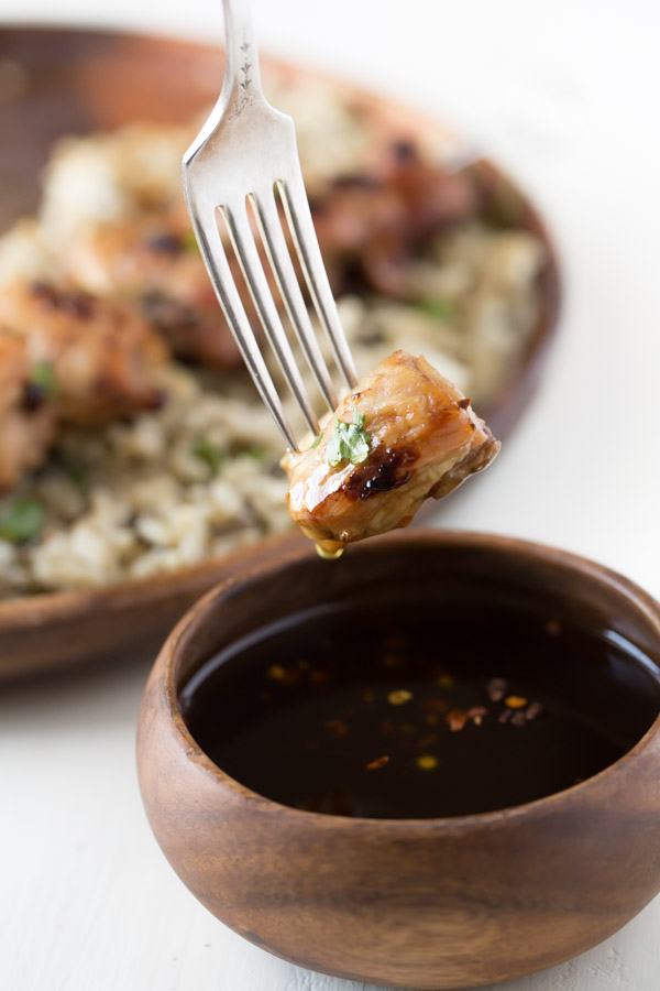 A piece of Maple Dijon Glazed Chicken on a fork that has been dipped into a small bowl of the Maple Dijon Glaze.