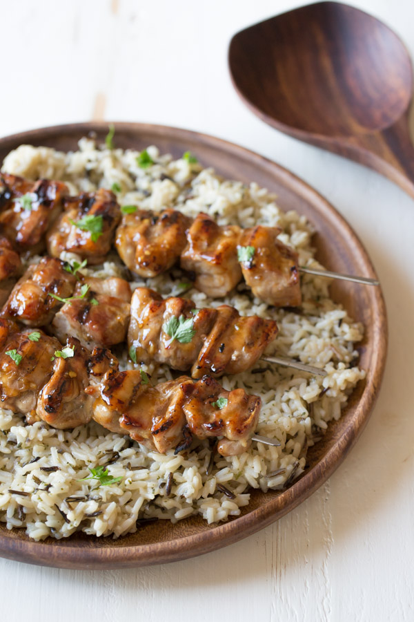 Maple Dijon Glazed Chicken served over a bed of rice on a wood plate.