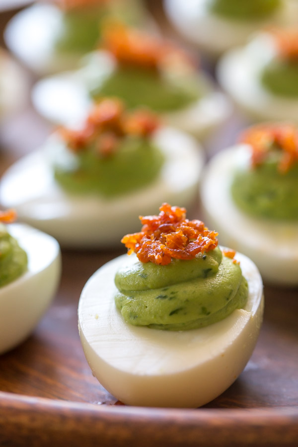 Smoky Bacon Avocado Deviled Eggs arranged on a wood plate.