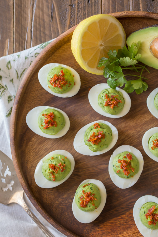 Smoky Bacon Avocado Deviled Eggs arranged on a wood serving plate, with a half of an avocado, a half of a lemon and a little bunch of cilantro.