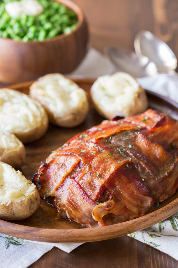Bacon Wrapped Meatloaf on a wood serving plate with five twice baked potatoes, and a bowl of peas in the background.