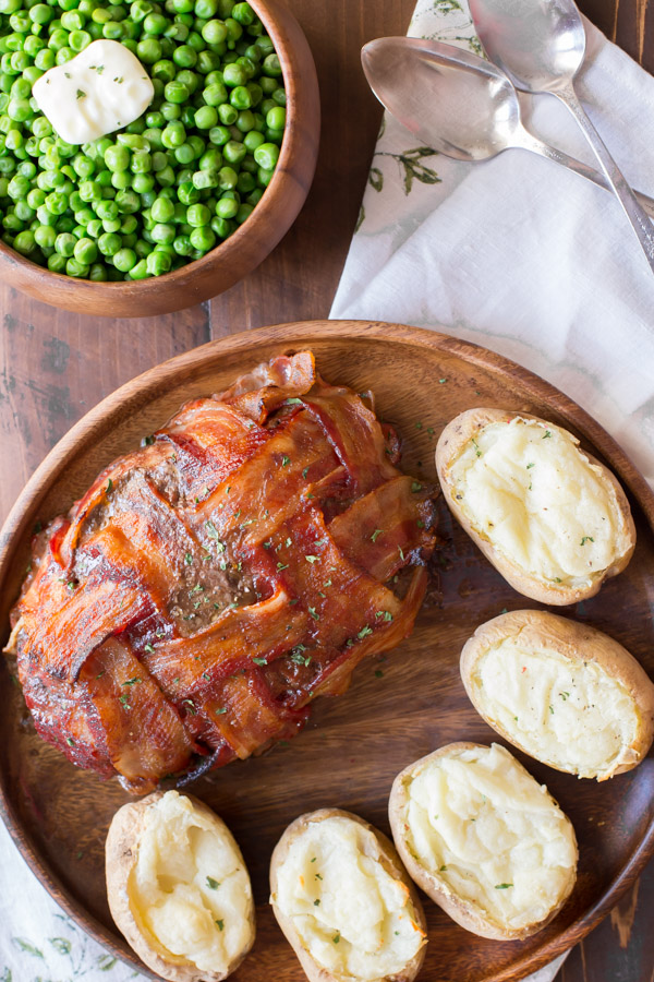 Bacon Wrapped Meatloaf on a wood serving plate with five twice baked potatoes, and a bowl of peas next to it.