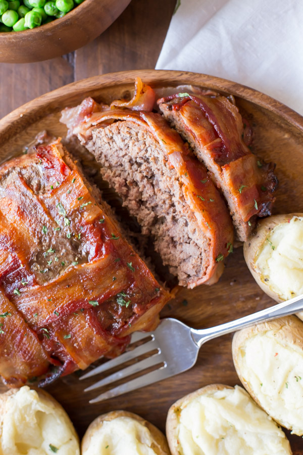 Bacon Wrapped Meatloaf that has been sliced on a wood serving plate with five twice baked potatoes and a fork, and a bowl of peas next to it.