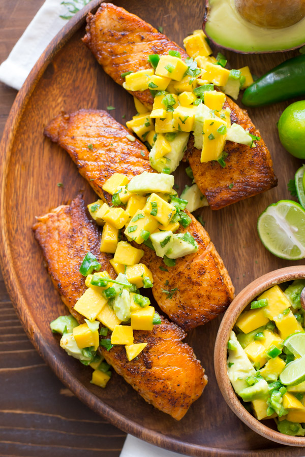 Chili Lime Salmon With Mango Avocado Salsa on a wood serving plate, with a half of an avocado, a jalapeño, a few limes, and a small wood bowl of the Mango Avocado Salsa.