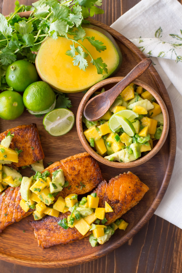 Chili Lime Salmon With Mango Avocado Salsa on a wood serving plate, with a half of a mango, a few limes, a bunch of cilantro and a small wood bowl of the Mango Avocado Salsa.