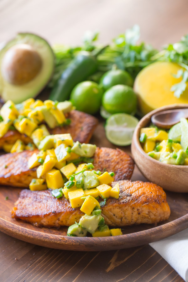 Chili Lime Salmon With Mango Avocado Salsa on a wood serving plate, with a half of an avocado, a jalapeño, a few limes, some cilantro, a half of a mango, and a small wood bowl of the Mango Avocado Salsa.