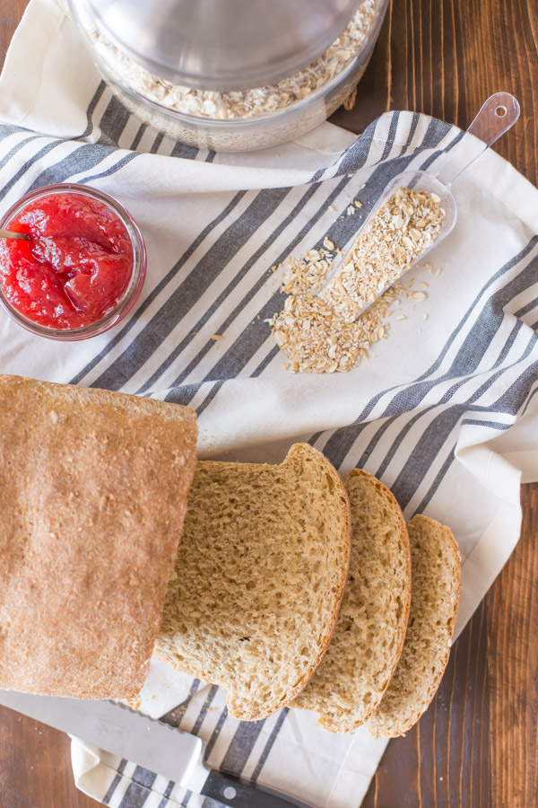 Easy Honey Whole Wheat Bread loaf that has been sliced, sitting on a cloth towel with oats and a jar of jelly.