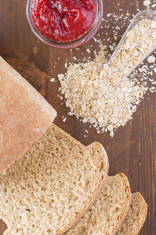 Easy Honey Whole Wheat Bread loaf that has been sliced, sitting next to some oats and a jar of jelly.