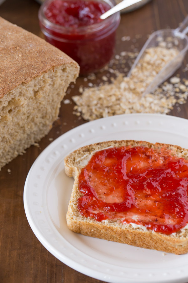 A slice of Easy Honey Whole Wheat Bread with butter and jelly on a plate, sitting next to the loaf of bread, the jar of jelly and some oats.