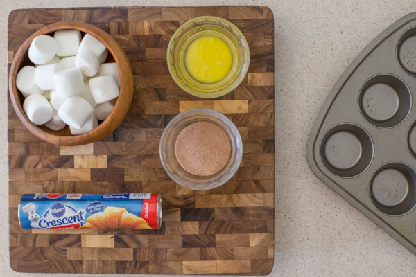 Empty Tomb Roll ingredients on a cutting board next to a muffin tin.